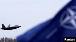 지난달 27일 리투아니아 내 군사기지에 나토(NATO. 북대서양조약기구) 깃발이 휘날리는 가운데 미 공군 F-22 전투기가 비행하고 있다.