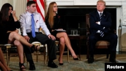 Parent Melissa Blank, from left, and Marjory Stoneman Douglas High School shooting surviving students Jonathan Blank and Julia Cordover attend with other survivors and the families of victims a listening session held by U.S. President Donald Trump to discuss school safety and shootings, at the White House in Washington, Feb. 21, 2018.