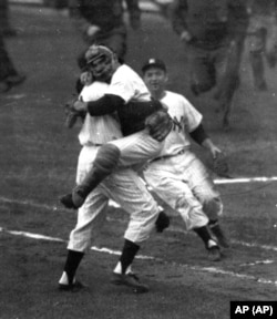 In this Oct. 8, 1956 photo, New York Yankees catcher Yogi Berra is embraced by pitcher Don Larsen as he leaps into Larsen's arms at the end of Game 5 of baseball's World Series against the Brooklyn Dodgers at New York's Yankee Stadium.