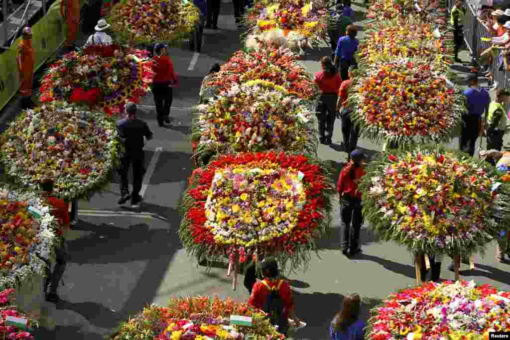Flower growers known as silleteros carry their flower arrangements during the annual flower parade in Medellin, Colombia, Aug. 10, 2014.