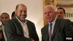 Perwakilan Fatah, Azzam al-Ahmed berjabat tangan dengan wakil pimpinan Hamas, Mussa Abu Marzuq setelah mengadakan konferensi pers di Kairo, Mesir (04/27)