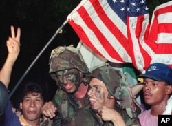 U.S. soldiers carry an American flag through the streets of Panama City as they celebrate with Panamanian citizens in Jan. 1990 following the surrender of Panamanian leader Manuel Noriega.