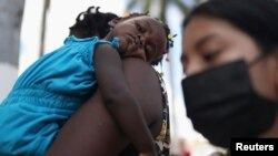 Yon timoun Ayisyen repoze nan bra manman ni, nan moman migran Ayisyen yo ap remet dokiman yo bay reprezantan sevis sosyal yo sou plas Benito Juarez nan Tapachula, Meksik, 14 Sept. 2021.