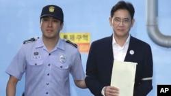 Miliuner pewaris Samsung, Lee Jae-yong (kanan), meninggalkan gedung pengadilan di Seoul dengan diborgol dan dikawal polisi akhir Agustus lalu (foto: dok).