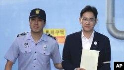 Wakil Pimpinan Samsung Electronics Co., Lee Jae-yong (kanan) meninggalkan Pengadilan Distrik Pusat, Seoul, Korea Selatan, 25 Agustus 2017. Lee divonis lima tahun penjara terkait penyuapan dalam skandal yang menjatuhkan presiden negara tersebut.