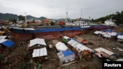 FILE - Typhoon survivors living in temporary shelters are seen near ships that ran aground, nearly 100 days after super Typhoon Haiyan devastated Tacloban city in central Philippines, Feb. 14, 2014.