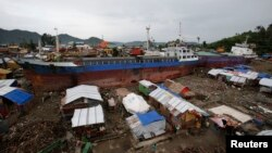 FILE - Typhoon survivors living in temporary shelters are seen near ships that ran aground, nearly 100 days after super Typhoon Haiyan devastated Tacloban city in central Philippines.