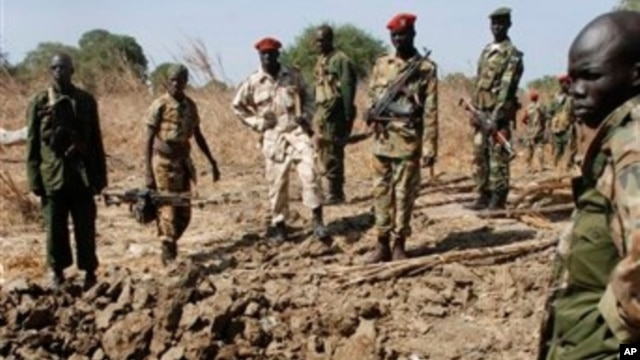 Southern army officers in Northern Bahr el Ghazal state in Sudan, peer into a bomb crater created from one of the bombs dropped by the northern Sudanese army on a southern army base in the disputed border zone of Kiir Adem, where Southern Sudan meets Darf