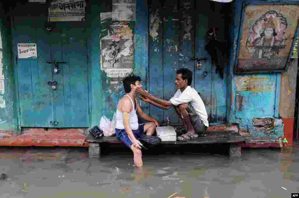 A barber shaves a customer in his temporary shop alongside a water-logged street in Kolkata, India.