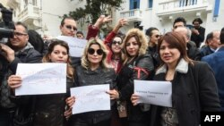 "Tunisian journalists wearing red armbands protest with signs outside the headquarters of the National Union of Tunisian Journalists against police threats and intimidation in the capital Tunis on Feb. 2, 2018, holding signs reading in Arabic and French: ""The Tunisian press is angry."""