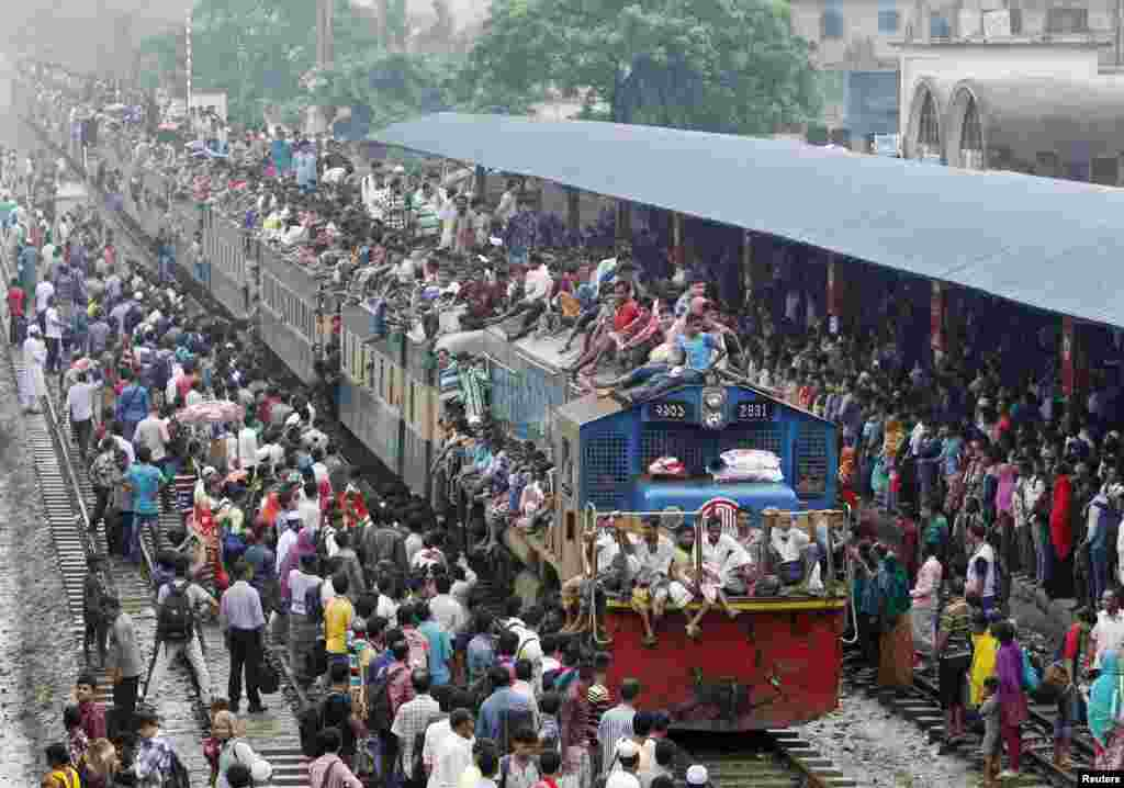 People crowd on top of a train entering the Dhaka airport rail station as thousands of Bangladeshi Muslims head home to celebrate Eid-al-Adha.