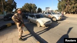 A security officer patrols the city ahead of Libya's two-year anniversary marking the ouster of Moammar Gadhafi, Benghazi, Feb. 12, 2013.