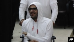 FILE - Mohamed Soltan, in a wheelchair, makes a court appearance in Cairo, Egypt, March 9, 2015.