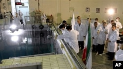 In this photo released by the Iranian President's Office, Iranian President Mahmoud Ahmadinejad, right, is escorted by technicians during a tour of Tehran's research reactor center in northern Tehran, Iran, February 15, 2012.