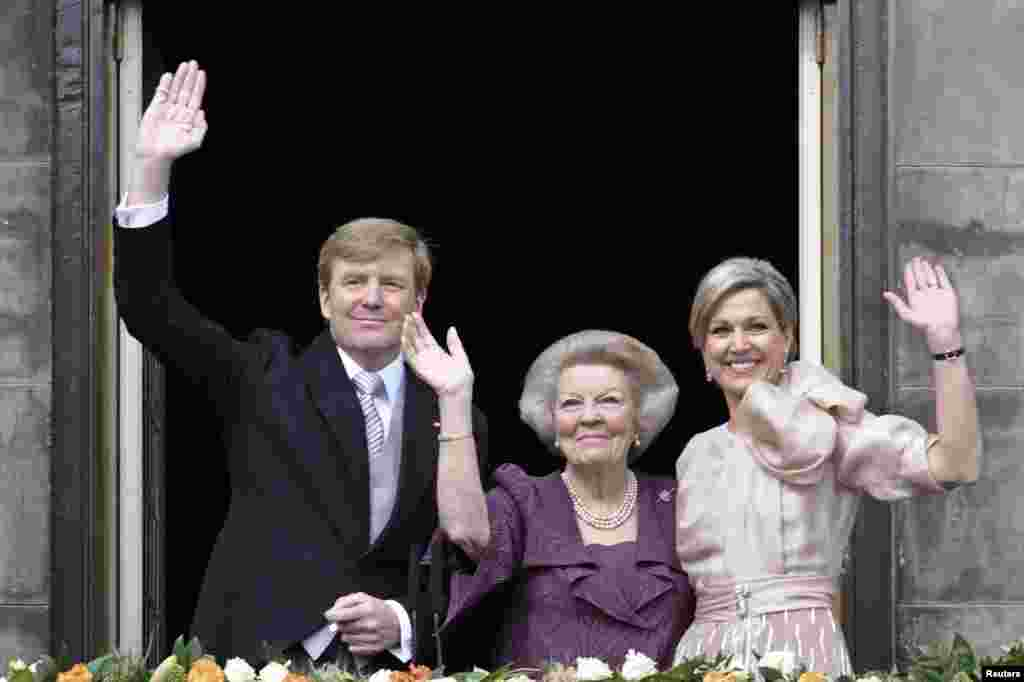 Princess Beatrix of Netherlands (C), her son, Dutch King Willem-Alexander (L) and his wife Queen Maxima wave to the crowd from the balcony of the Royal Palace in Amsterdam.