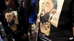 Guests wear T-shirts in tribute to Nipsey Hussle, whose given name was Ermias Asghedom, at the late rapper's Celebration of Life memorial service, April 11, 2019, at the Staples Center in Los Angeles.