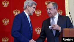 Menlu AS John Kerry (kiri) menjabat tangan Menlu Sergei Lavrov pada acara konferensi pers bersama di Moskow, Rusia 15 Desember 2015 (foto: dok).