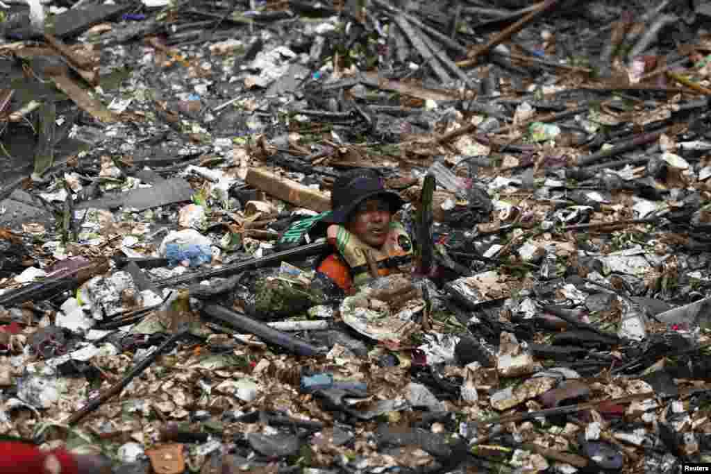 Seorang relawan berusaha membersihkan timbunan sampah di Sungai Ciliwung, Jatinegara, Jakarta.