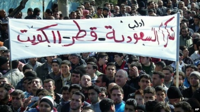 "In this Friday, March 2, 2012 citizen journalism image provided by the Local Coordination Committees in Syria, anti-Syrian regime protesters hold up a banner in Arabic reading: ""thank you Saudi Arabia, Qatar and Kuwait,"" during a demonstration, in Idlib,"