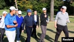 Presiden Donald Trump (Kanan) berbincang dengan Perdana Menteri Jepang Shinzo Abe (empat dari kanan), didampingi pegolf profesional Jepang, Hideki Matsuyama, pada saat bermain golf di Kasumigaseki Country Club di Kawagoe, dalam foto yang dirilis Kantor Humas Kabinet Jepang, via Kyodo, 5 November 2017. (Foto: Humas Kabinet Jepang via Kyodo, via Reuters)
