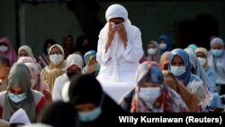 An Indonesian Muslim reacts during mass prayer session at the Great Mosque of Al Azhar during Eid al-Fitr, marking the end of the holy fasting month of Ramadan, amid the coronavirus disease (COVID-19) pandemic in Jakarta, Indonesia, May 13, 2021