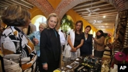 U.S. Secretary of State Hillary Rodham Clinton, second from left, admires items made by women entrepreneurs as she is greeted by some of the women before the media launch of the Women's Entrepreneurship in the Americas program in Cartagena, Colombia.