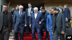 Iranian Foreign Minister Mohammad Javad Zarif, center, and his German counterpart Frank-Walter Steinmeier, center left, leave the Munich Security Conference venue in Tehran, Iran, Saturday, Oct. 17, 2015.
