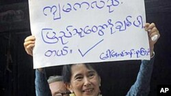 Burmese pro-democracy leader Aung San Suu Kyi displays a placard that reads, 'I also Love the People,' 14 Nov 2010။