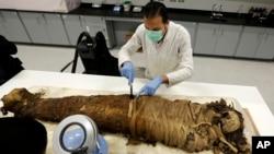 Des restaurateurs égyptiens nettoient une momie datée de la fin de la période pharaonique (712-323 av. J.-C.), dans le centre de conservation du grand musée égyptien en construction, juste à l'extérieur du Caire, Égypte, 17 mars 2014.
