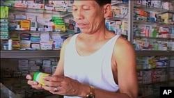 Cambodian man purchases malaria medicine at local pharmacy