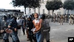 La police anti-émeute libanaise arrête un manifestant anti-gouvernemental, qui tentait d'atteindre le bâtiment du Parlement, lors d'une manifestation contre les élites politiques et le gouvernement, à Beyrouth, au Liban, le samedi 8 août 2020. (Photo AP / Hussein Malla)