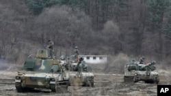 韩国军人在坡州附近的年度军演之际站在K-55自行榴弹炮上。(2016年3月7日)