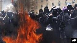 Female Yemeni protesters burn veils during a demonstration demanding the resignation of Yemeni President Ali Abdullah Saleh in Sana'a, Yemen, October 26, 2011.