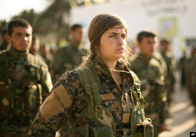 Сирийские демократические силы, поддерживаемые США, стоят в строю на церемонии по случаю поражения боевиков Исламского государства в Багхузе, на базе нефтяного месторождения Аль-Омар, Сирия, 23 марта 2019 года.