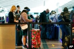FILE - Travelers wear face masks while waiting to check in at the Southwest Airlines counter in Denver International Airport, Dec. 22, 2020, in Denver.