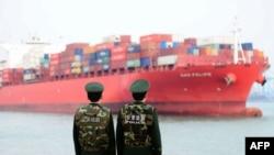 Oficiales de policía chinos observan un barco de carga en un puerto en Qingdao, en la oriental provincia china de Shandong. Foto de archivo, 8 de marzo, de 2018.