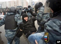 FILE - Policeman detain a protester during a march to mark National Unity Day, in Moscow, Russia, Nov. 4, 2013. Several thousand Russian nationalists rallied against the migrants they accuse of pushing up the crime rate and taking their jobs.