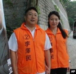 香港區議會選舉候選人李澤民(左)與太太一起進行競選工作