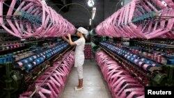 Employee works inside silk factory in Neijiang, Sichuan province, July 3, 2013.