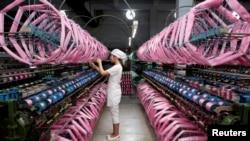 Công nhân làm việc bên trong nhà máy sản xuất tơ lụa ở Nội Giang, tỉnh Tứ Xuyên.