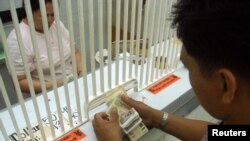 A customer counts Philippine pesos at a money changer in Manila, (File photo).