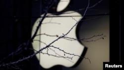 ARSIP – Logo perusahaan Apple tampak di balik cabang-cabang pohon di luar toko Apple di Beijing, 14 Desember 2018 (foto: Reuters/Jason Lee/Foto Arsip)