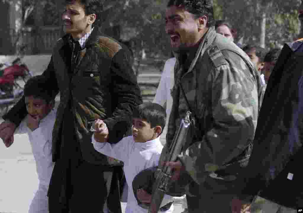 A police officer shouts as children are rescued following a suicide attack on a church in Quetta, Pakistan, Sunday, Dec. 17, 2017.