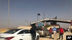FILE - Jordanian cars prepare to cross into Syria, at the Jordanian-Syrian border Jaber crossing point, in Mafraq, Jordan, Oct. 15, 2018.