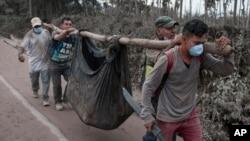 Stanovnici nose telo osobe stradale u erupciji vulkana Fuego u Eskintli, u Gvatemali (Foto: AP/Oliver de Ros)