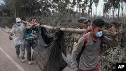 Residentes llevan un cuerpo recuperado cerca del Volcán de Fuego en Escuintla, Guatemala, el lunes, 4 de junio de 2018.