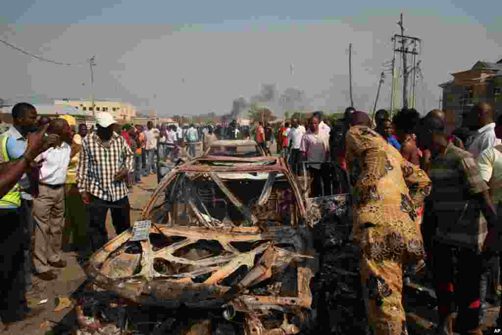 Onlookers stand by a destroyed car at the site of a bomb blast at St. Theresa Catholic Church in Madalla, Nigeria. (AP)