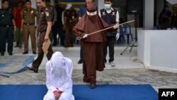 Perempuan pertama yang menjadi algojo hukum cambuk bersiap mencambuk seorang perempuan di Banda Aceh, 10 Desember 2019. (Foto: AFP)