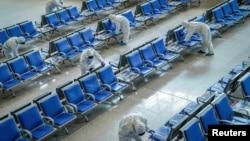身穿防護服的工人在武漢火車站給座椅消毒,為武漢開城做準備。(2020年3月25日)