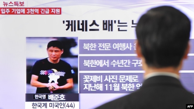 A passerby watches a local television broadcast in Seoul on May 2, 2013 showing a report and picture of Kenneth Bae (L), a Korean-American tour operator detained in North Korea.